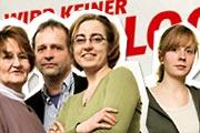 Vier Menschen vor einem Plakat