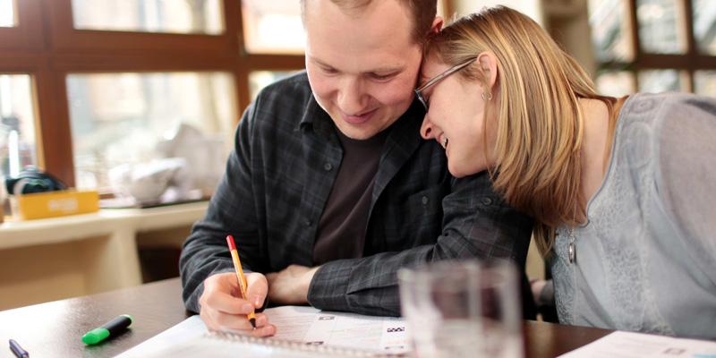 Ein Mann füllt ein Blatt Papier aus. Eine Frau sitzt neben ihm, lächelt ihn an und legt ihren Kopf auf seine Schulter.