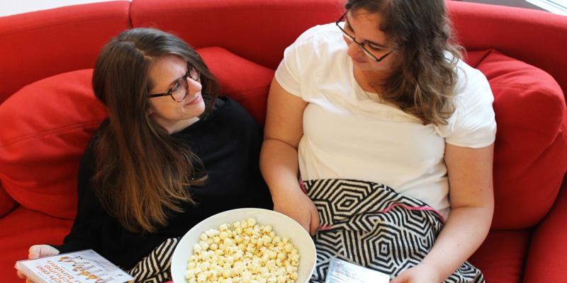 Zwei junge Frauen, die auf einer Couch sitzen. In der Hand haben sie verschiedene DVD-Hüllen und eine Schale Popcorn.
