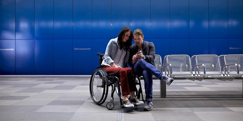 Eine Frau im Rollstuhl und ein Mann sitzen an einer Bahnhaltestelle und schauen auf ein Handy.