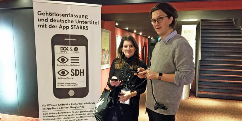 """Lena und Wille stehen im Flur eines Kinos neben einem Plakat mit der Aufschrift """"Gehörlosenfassung und deutsche Untertitel mit der App STARKS"""". In ihren Händen halten sie ihre Smartphones."""