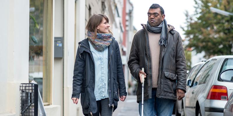 Eine Frau und ein Mann mit Blindenstock gehen über die Straße und lächeln sich an.