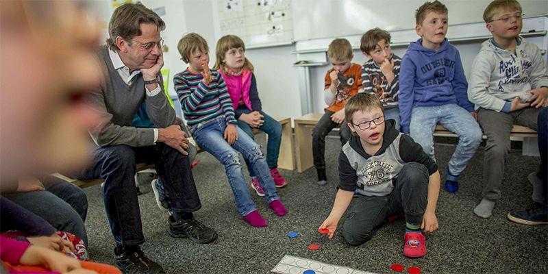 Grundschüler sitzen mit Rudi Cerne im Klassenraum