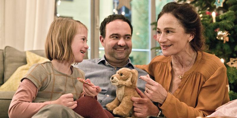 Eine Familie aus Mann, Frau und Mädchen mit Down-Syndrom sitzt auf dem Sofa und lächelt sich an.