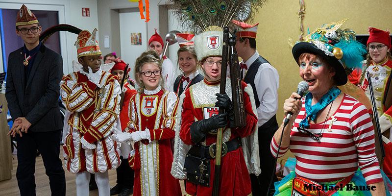 Karneval: Eine als Clown verkleidete Frau mit Mikro in der Hand steht auf einer Bühne neben drei als Prinz, Jungfrau und Bauer verkleideten Kindern.