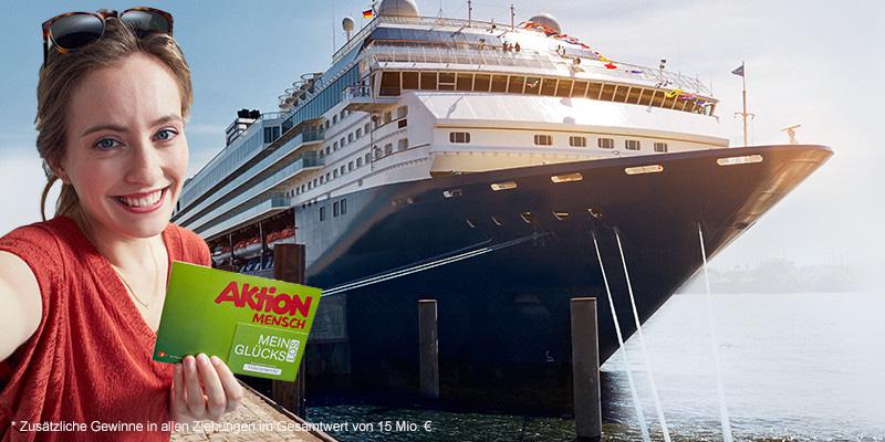 Eine junge Frau steht vor einem Schiff. Mit einem Glücks-Los in der Hand lacht sie in die Kamera.