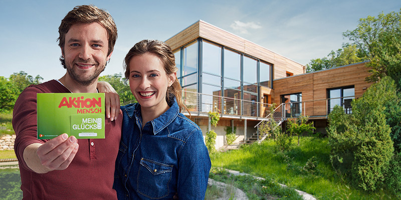 Ein Paar steht vor einem Traumhaus und hält ein Glückslos in den Händen