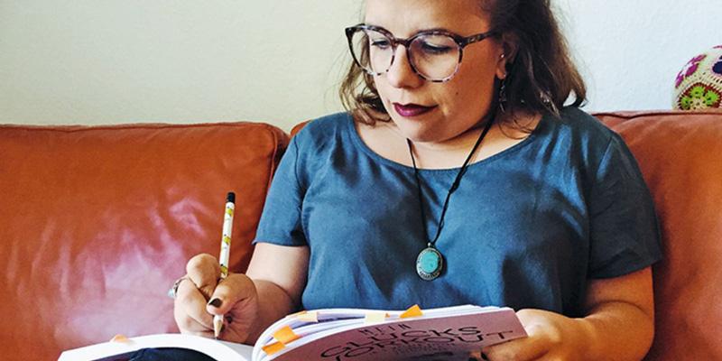 """Eine Frau liest ein Buch mit dem Titel """"Mein Glücks-Workout"""""""