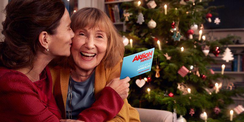Frau küsst eine ältere Frau und hält ein Jahreslos in der Hand