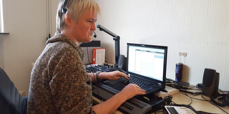 Eine Frau mit Headset tippt auf einem Laptop.