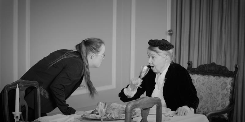 Eine Frau mit Down-Syndrom schaut einer älteren Frau, die aus einem Weinglas trinkt, in die Augen. Die ältere Frau sitzt am Tisch.