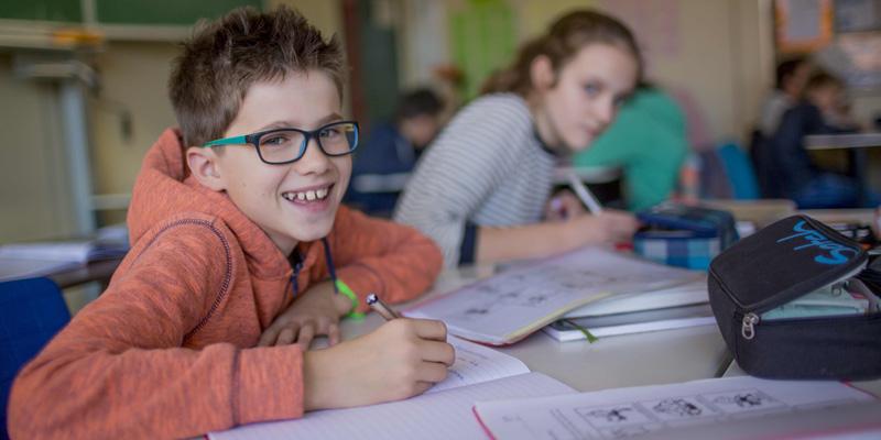 Ein Junge sitzt am Schultisch und schreibt in ein Schulheft.