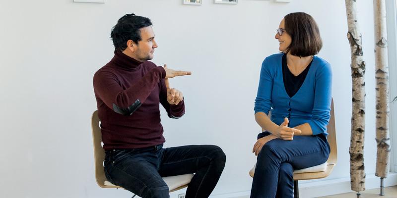 Eine Frau und ein Mann unterhalten sich in Gebärdensprache.