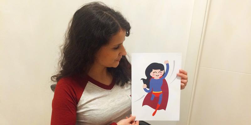 Eine Frau im Rollstuhl hält ein Blatt Papier mit einem Superhelden-Emoji mit einem Bein in der Hand.