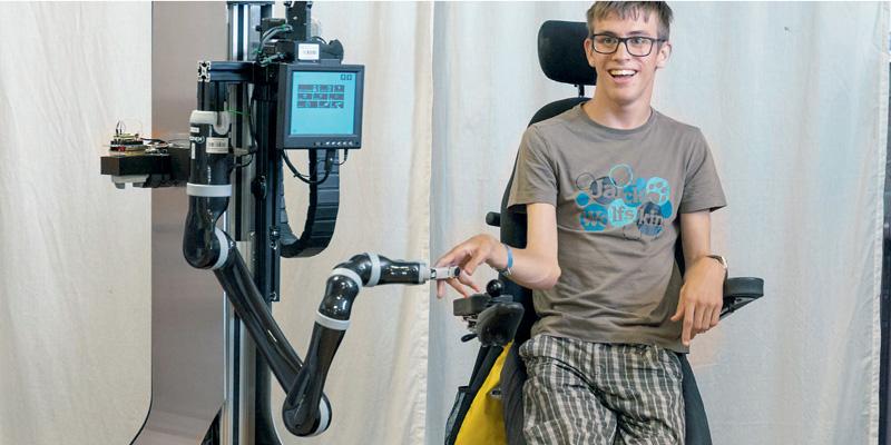 Ein Junge im Rollstuhl gibt einem Roboter die Hand.