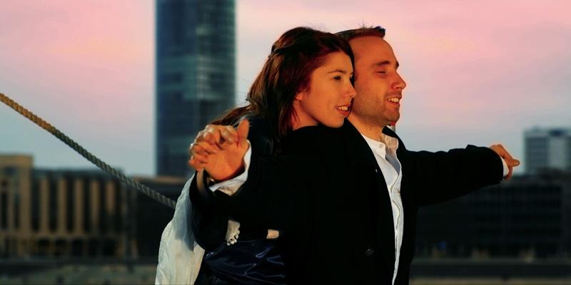 Eine Frau steht hinter einem Mann, der die Arme zu beiden Seiten ausgestreckt und die Augen geschlossen hat.