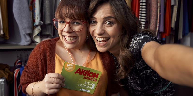 Zwei Frauen lächeln in die Kamera und halten das Glücks-Los hoch.