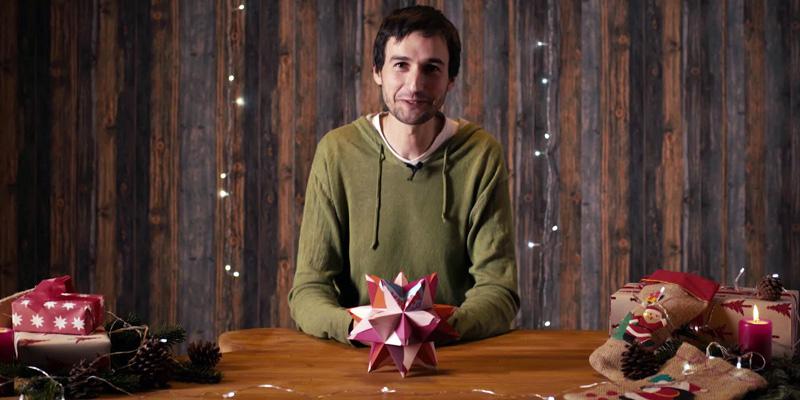 Ein Mann sitzt an einem Tisch. Vor ihm liegt ein Origami-Stern.
