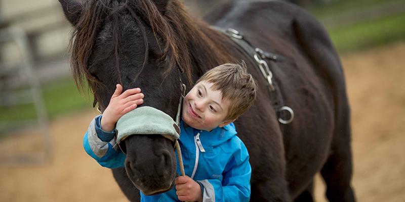 Ein Junge mit Down-Syndrom umarmt ein Therapie-Pferd