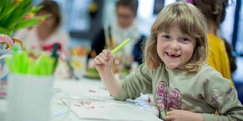 Ein Mädchen mit Zahnlücken lächelt in die Kamera.