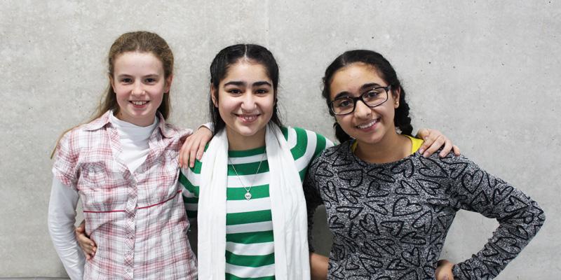 Drei Schülerinnen stehen vor einer grauen Wand und lächeln in die Kamera.