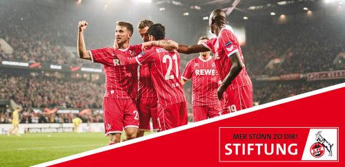 1. FC Köln: Spieler auf dem Feld und Fussball-Logo